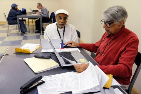A volunteer helps a man fill out his income tax return at the Southwest Neighborhood Library in Washington
