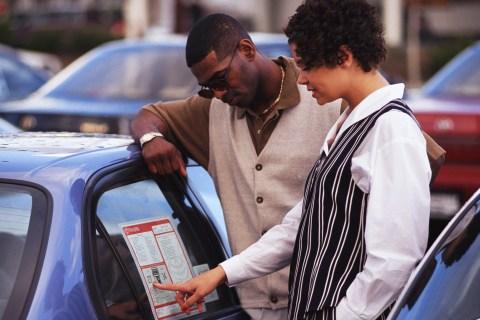Couple Checking a Car's Sticker Price