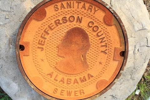 A manhole cover bears the logo/design of Jefferson County, Alabama
