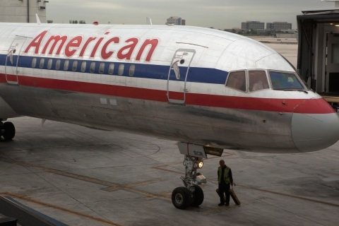 A worker walks underneath an American Airlines airplane at Miami International airport in Miami, Florida