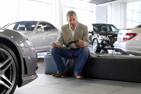 Man looking at brochure at car dealership