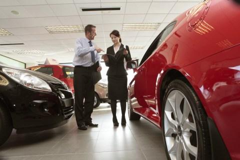 Woman talking to salesman in car showroom