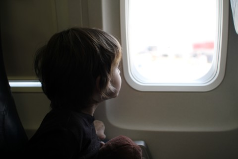 Child sitting by window in airplane