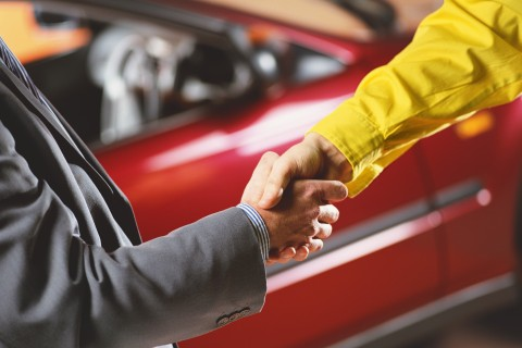 car salesman and buyer shaking hands