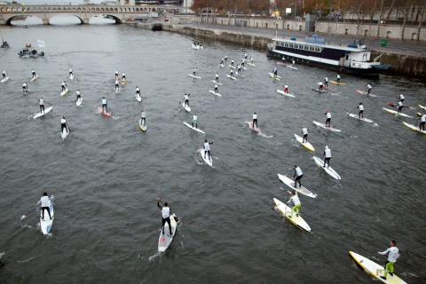 Competitors take part in a stand up paddle race