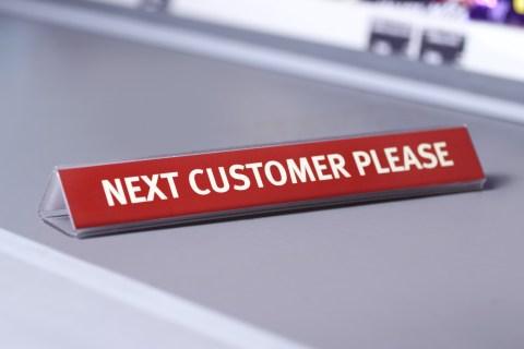 Next customer sign at supermarket checkout