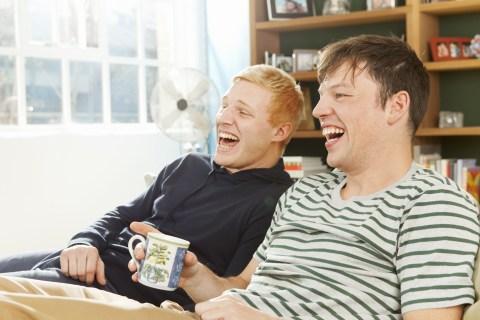 Men laughing watching TV