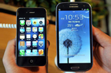 An employee shows an Apple's iPhone 4s, left, and a Samsung's Galaxy S3