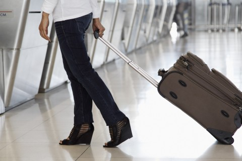 close up of woman with luggage at airport counter