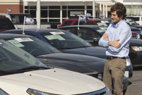 Young man on car dealership lot