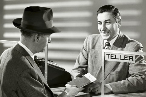 Mature man handing a bank book to a bank teller
