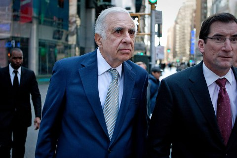 image: Carl Icahn walks outside of the Nasdaq MarketSite with Robert Greifeld, chief executive officer and president of Nasdaq OMX Group Inc., in New York, March 27, 2012.