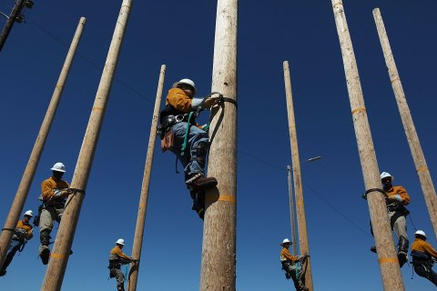 image: Students participating in Pacific Gas and Electric's PowerPathway Pole Climbing Capstone course climb utility poles at the PG&E pole climbing training facility in Oakland, Calif., June 8, 2012.