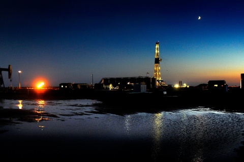 image: An oil drilling rig at dusk near New Town, North Dakota on June 29, 2012.