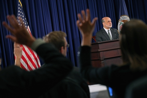 Reporters raise their hands to ask Federal Reserve Chairman Ben Bernanke a question during a press conference