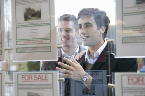 Couple looking into estate agents window
