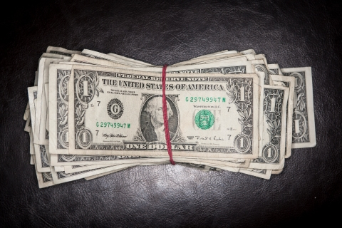 Overhead shot of one dollar bills sitting on a leather background with a red rubber band.