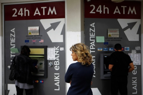 A woman waits as  two people use the ATM machines in central capital Nicosia, Cyprus, on March 22, 2013.