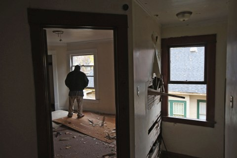 A homeless man looks from the window of a condemned house in Warren, Ohio, Oct. 28, 2012.