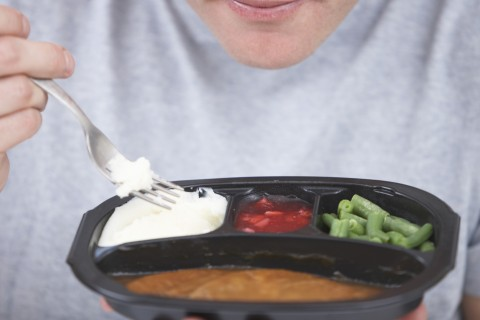 Young man eating TV dinner, mid section