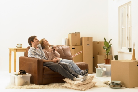Young couple with moving boxes in new house