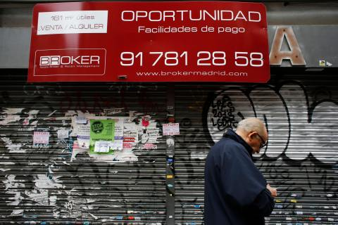 A man walks past a closed down business in Madrid