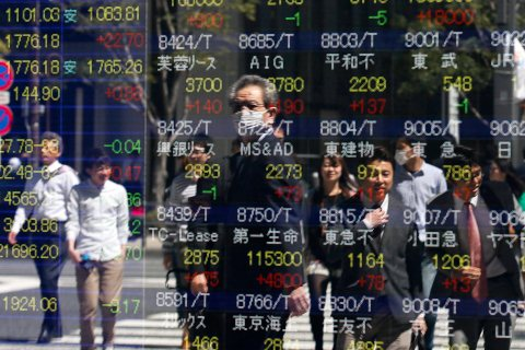 Pedestrians are watching Tokyo stock indexes on a public display board in Tokyo, April 8, 2013.