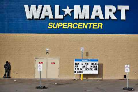 A man stands on a skateboard outside a Wal-Mart store in Williston, North Dakota
