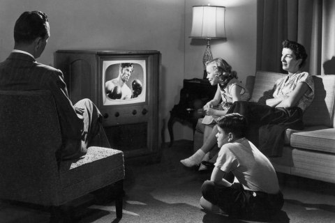 A family of four watches a boxing match on television