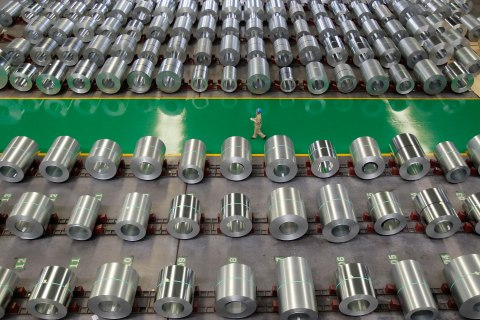 An employee walks past rows of steel at a steel production factory in Wuhan, Hubei province, Aug. 2, 2012.