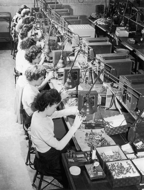Female factory workers assembling machine parts in an American factory during World War II in 1942.
