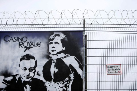 File photo of graffiti depicting ECB President Draghi and German Chancellor Merkel is seen outside the new ECB headquarters in Frankfurt