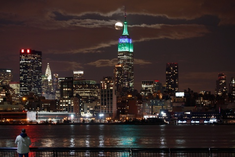 A full moon rises behind the Empire State Building in New York as a man watches in a park along the Hudson River in Hoboken, New Jersey