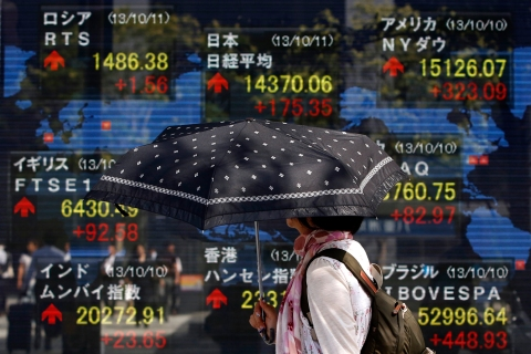 A pedestrian holding an umbrella walks past a stock quotation board displaying various countries' share prices outside a brokerage in Tokyo