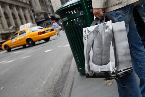A man holds a shopping bag from  Abercrombie & Fitch outside their store in New York