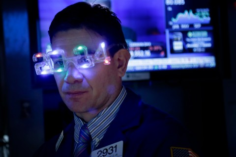A trader wears glasses celebrating the new year while working on the floor at the New York Stock Exchange in New York City, on Dec. 31, 2013.