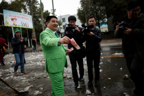 Chinese multimillionaire Chen Guangbiao gives money away to street cleaners during an event he organized in Nanjing, Jiangsu province Feb. 21, 2013.