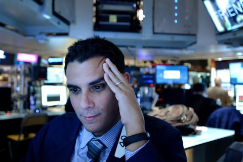 A trader works on the floor of the New York Stock Exchange at the end of the trading day in New York,  Jan. 24, 2014.