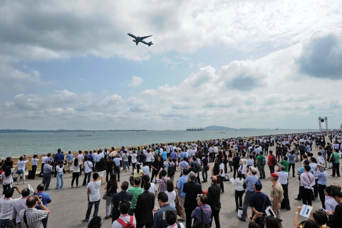 Visitors watch as a Airbus A350 flies past during the Singapore Airshow on Feb. 12, 2014.