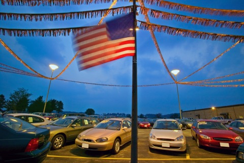 New and used cars in dealership parking lot, dusk